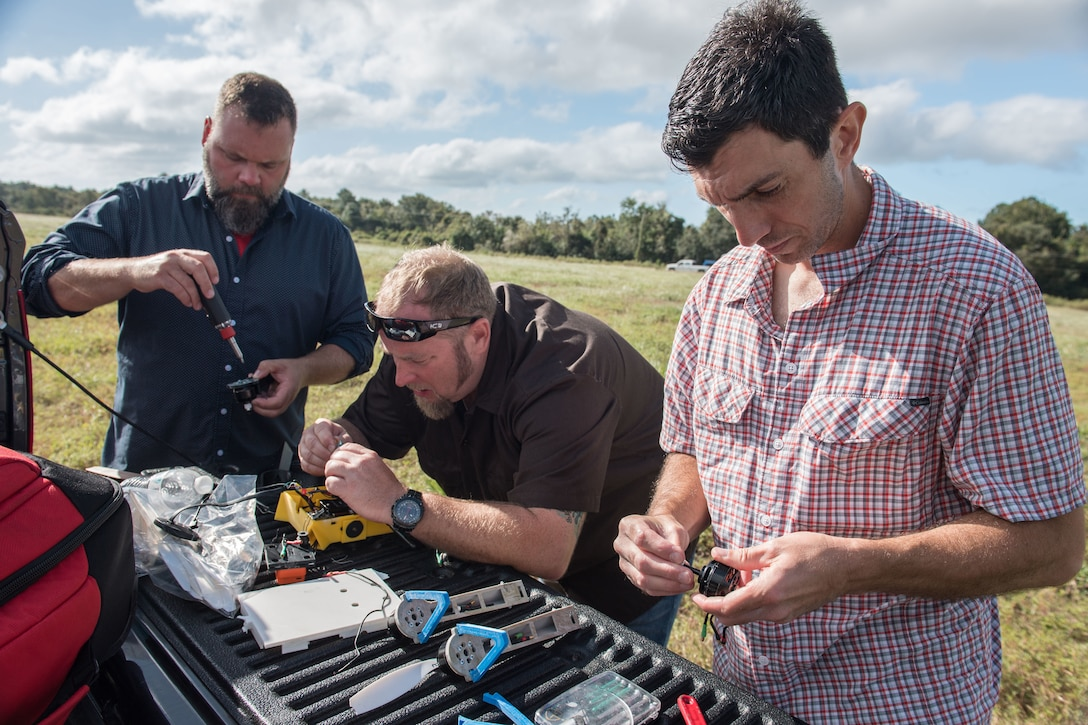 Three men use hand tools on small electronic devices in a field.