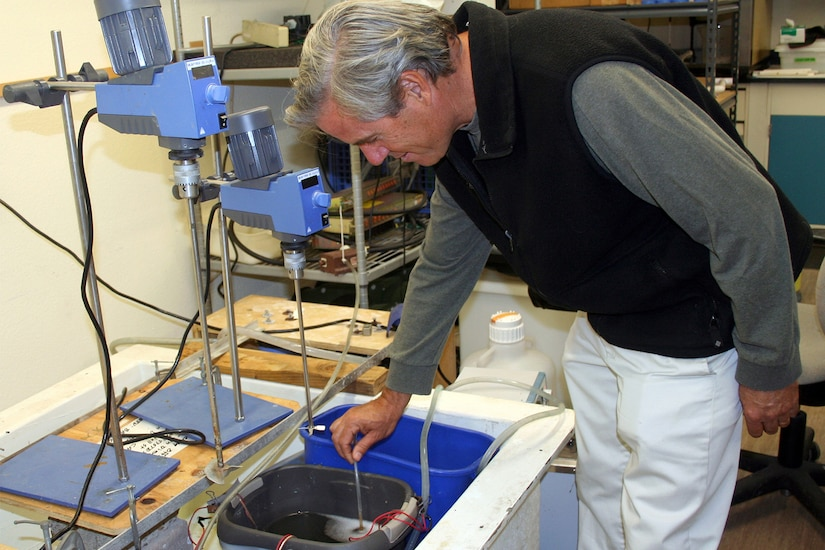 The head of the Environmental Sciences Branch Space at the Naval Warfare Systems Center checks fuel cells in a container.