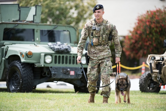 Staff. Sgt. Luke Gibson, 30th Security Forces Squadron military working dog handler, walks MWD Aramis during the Police Week Expo May 15, 2019, at Vandenberg Air Force Base, Calif. The Expo included a K-9 demonstration, which showcased the MWDs capabilities to take down a suspect. (U.S. Air Force photo by Airman 1st Class Hanah Abercrombie)