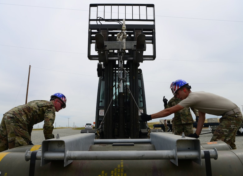 A photo of Airmen attaching a munition to a forklift.