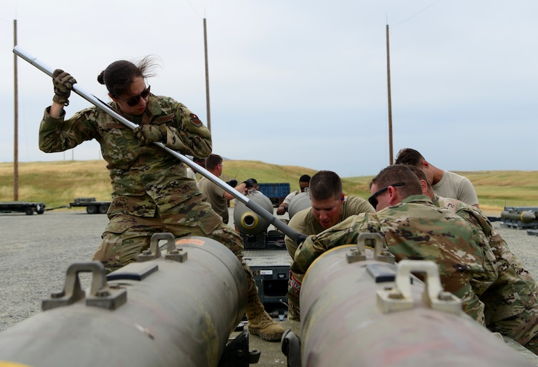 A photo of a team of Airmen assembling a munition on Beale.