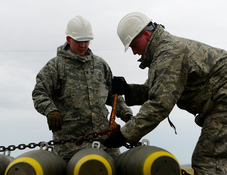 A photo of two Airmen tightening a chain on Beale.