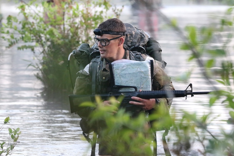 A soldier wearing goggles and a headband wades through a swamp while carrying a backpack, a map and a rifle.