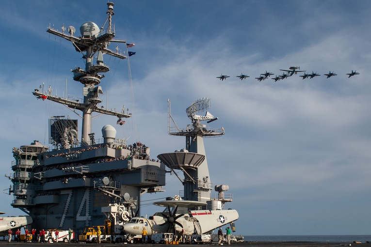 Eleven aircraft fly in formation as dozens of sailors watch from the bridge of an aircraft carrier.