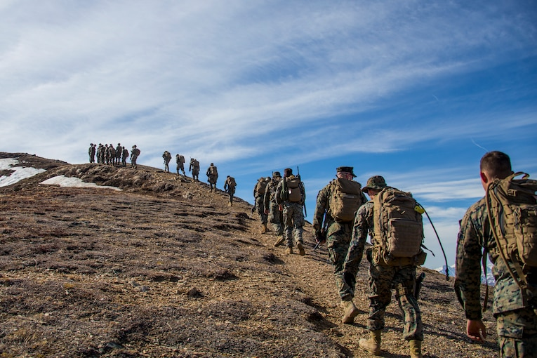 A group of Marines hike up a mountain.