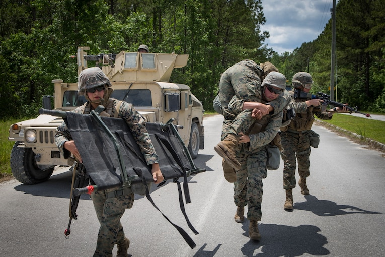 Three Marines walk past a vehicle carrying a stretcher, a rifle and a simulated casualty.