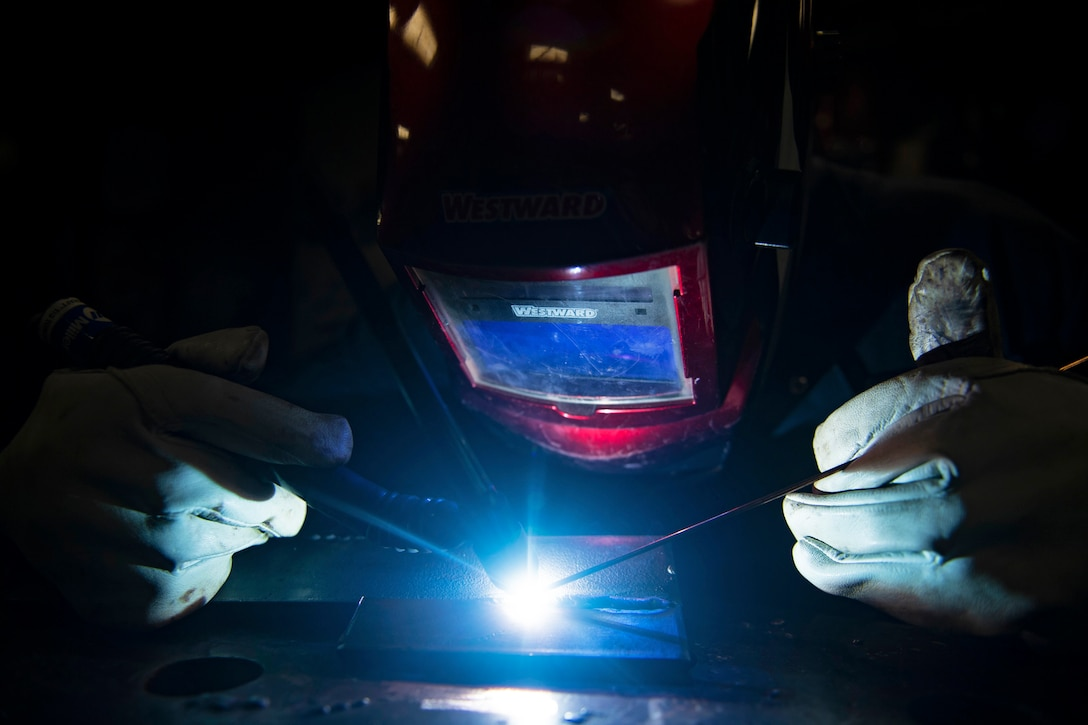 A welder works on a hatch lock at a table.