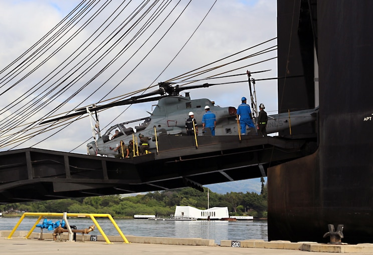 Several Marines are shown around a helicopter on a drawbridge.
