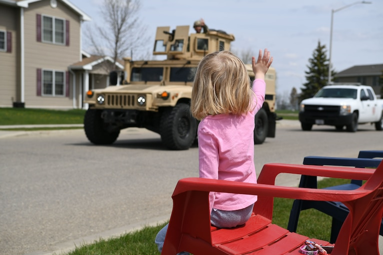 A child in a red lawn chair waves as an airman in a Humvee passes, followed by a pickup truck.