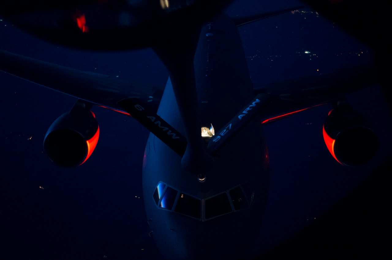 A refueling probe descends toward an aircraft in midair at night.