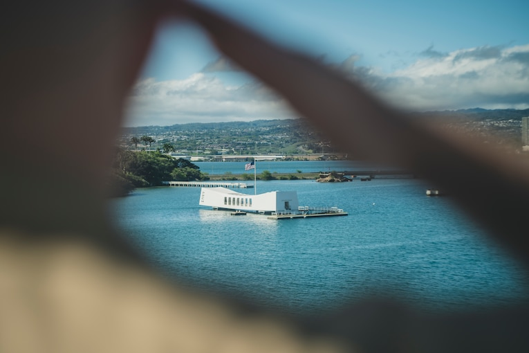 The USS Arizona memorial is seen through the saluting hand of a Marine.