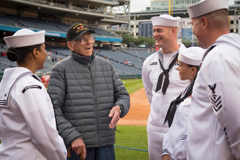 Four sailors and a veteran talk and laugh in a baseball field.