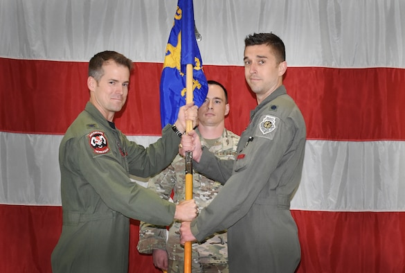 """Col. Joshua Wood, 388th Fighter Wing Operations Group commander, left, passes the guidon of the 34th Fighter Squadron to Lt. Col. Aaron Cavasos, as he takes command of the """"Rude Rams"""" May 17, 2019. Cavasos previously served as the director of operations for the squadron. The 34th Fighter Squadron was the first of the 388th FW units to stand up as an operational F-35A Lightning II Squadron in 2015. Cavasos is the 3rd commander since then. Lt. Col. Matthew Johnston relinquished command and is headed to another assignment in Washington, D.C."""
