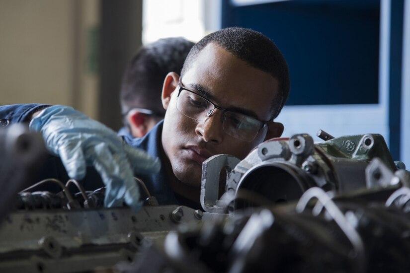 International students work on a diesel engine.
