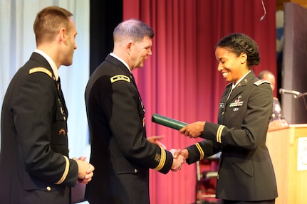 Maj. Kourtney Logan looks down at her graduation certificate presented by Maj. Gen. Todd B. McCaffrey, U.S. Africa Command chief of staff, during a U.S. Army Command and General Staff Officers Course Common Core graduation ceremony hosted by the 7th Intermediate Level Education Detachment, 7th Mission Support Command, in Grafenwoehr, Germany, May 17, 2019. The 7th ILE DET offers a unique year-long ILE common core curriculum designed for multi-component officers deployed or stationed overseas.