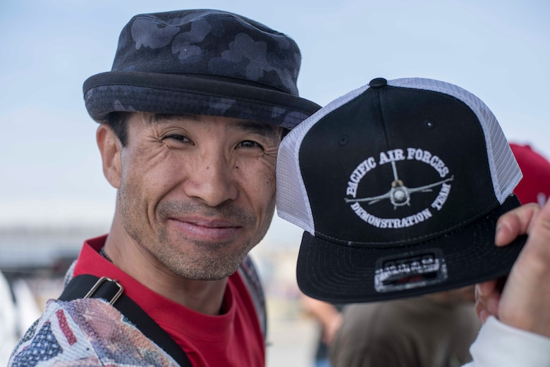 A 43rd Japan Maritime Self-Defense Force – Marine Corps Air Station Iwakuni Friendship Day 2019 guest holds a Pacific Air Forces Demonstration Team hat at MCAS Iwakuni, May 5, 2019. Attendees could purchase mementoes and souvenirs during the show. These items gave event spectators a way to promote and display their support for the PACAF F-16 Demo Team. (U.S. Air Force photo by Senior Airman Collette Brooks)