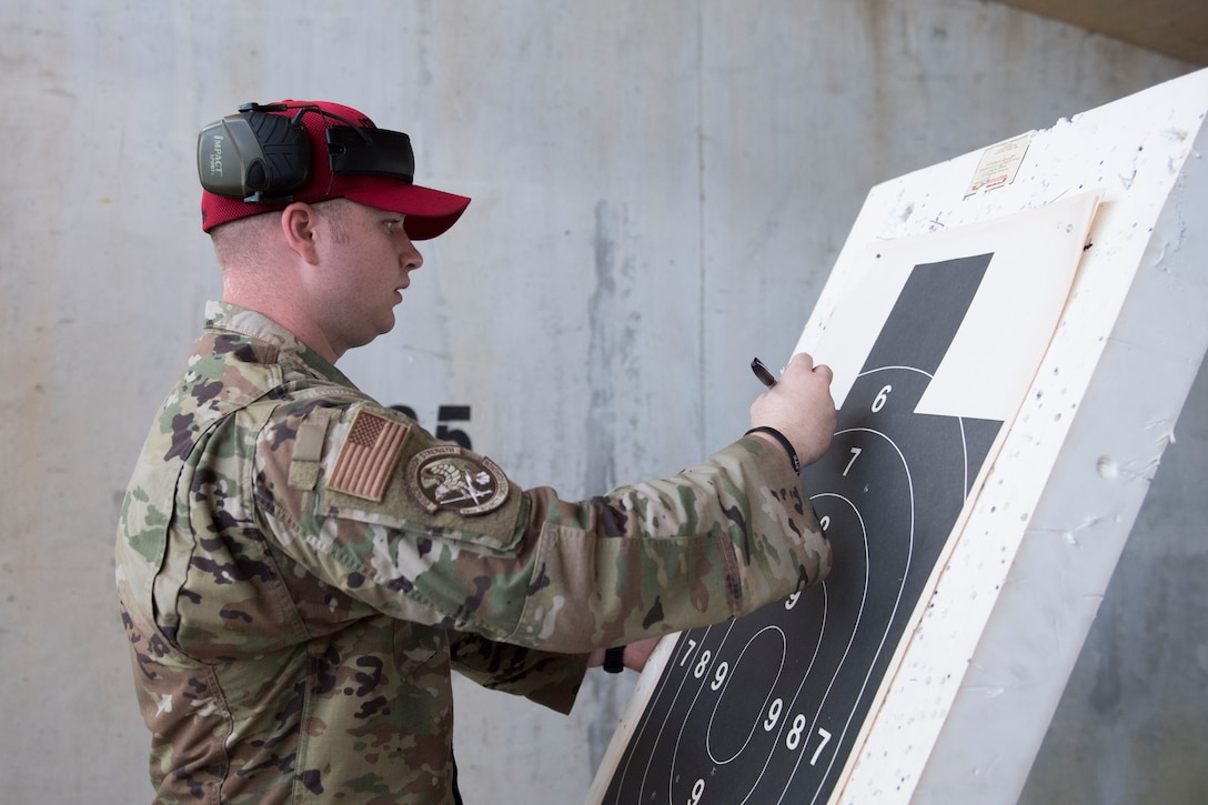 Senior Airman Preston Smith, 39th Security Forces Squadron combat arms instructor, counts bullet holes on a target during a shooting competition on May 17, 2019, at Incirlik Air Base, Turkey. The 39th SFS hosted the competition as part of the 39th Air Base Wing's Police Week observance. The purpose of Police Week is to honor the service of law enforcement officers and commemorate those who have fallen in the line of duty. (U.S. Air Force photo by Senior Airman Joshua Magbanua)