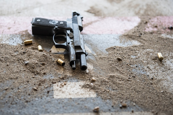 A handgun rests on the ground among shell casings during a shooting competition on May 17, 2019, at Incirlik Air Base, Turkey. The 39th Security Forces Squadron hosted the event, which was designed to give non-security forces Airmen a taste of the stress law enforcement officers feel when faced with using deadly force. (U.S. Air Force photo by Senior Airman Joshua Magbanua)