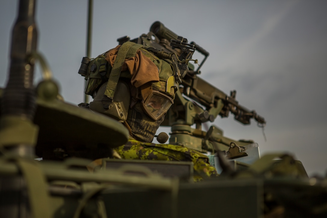 Canadian Army Capt. Dave Crosbie, a light armored vehicle captain with Charlie Company, 1st  Battalion Princess Patricia's Canadian Light Infantry, scans the terrain during a movement in exercise Maple Resolve in Camp Wainwright, Alberta, Canada, May 13, 2019. Maple Resolve is an annual exercise, 3-week multinational simulated war, hosted by the Canadian Army bringing NATO allies together from across the world to share and learn tactics while strengthening foreign military ties.