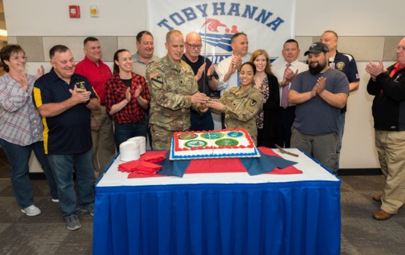 Depot employees stand watching the cake being cut with a sword.