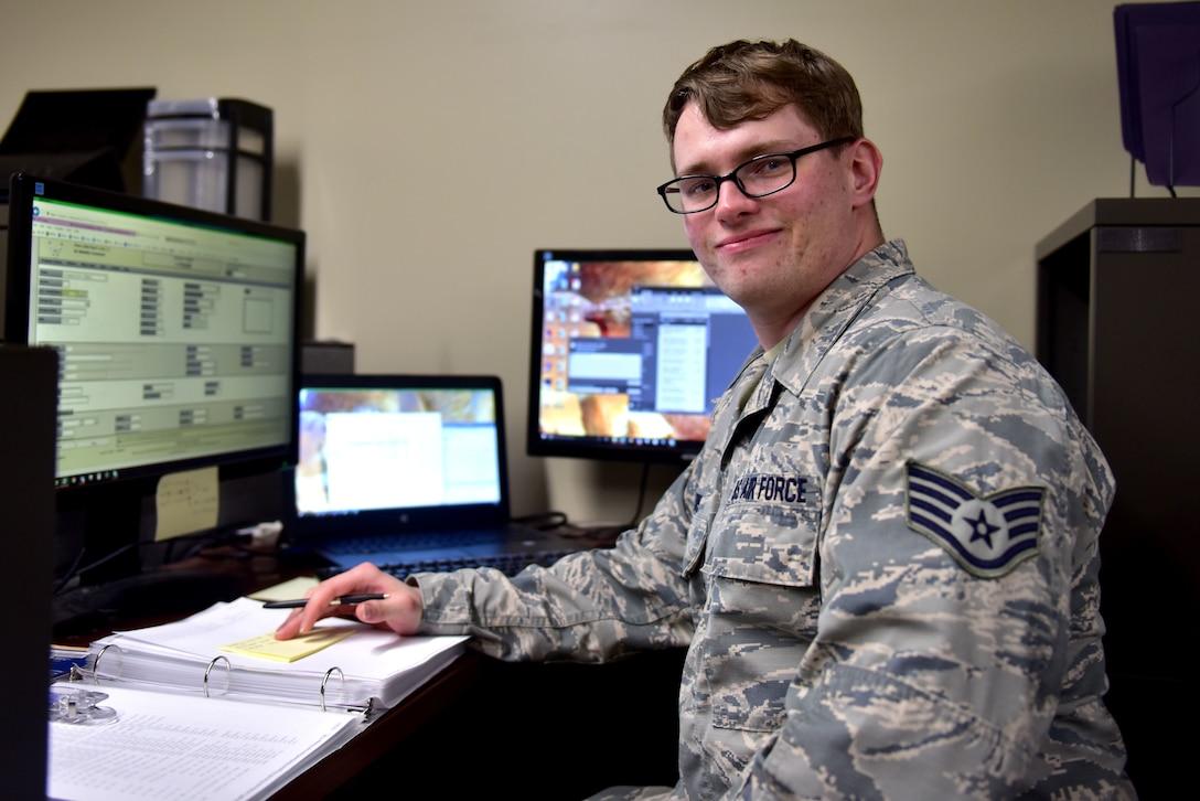 A man wearing the Airman Battle Uniform sits at a desk.