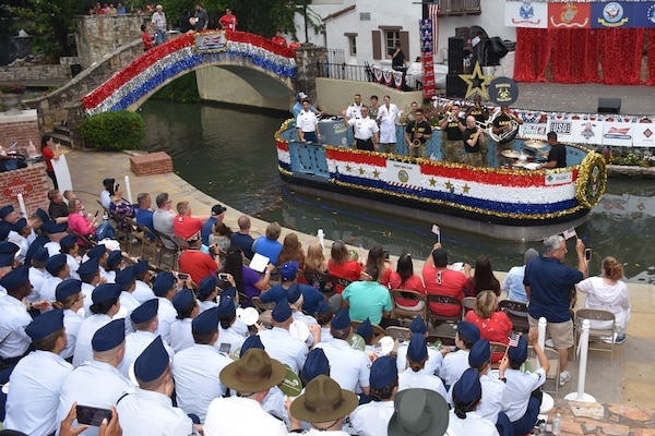 "Military members from Joint Base San Antonio enjoy the festivities at the Arneson River Theater during the annual Armed Forces River Parade May 18 in downtown San Antonio. This year's theme was ""Salute Our Heroes."" The parade promotes awareness of the joint presence and ties to the military families and community. Representing the U.S. Army in this year's parade were Brig. Gen. Bill Boruff, Mission and Installation Contracting Command commanding general; MICC Command Sgt. Maj. Marcos Torres, and Capt. Jim Jimenez, aide de camp for the MICC commanding general."