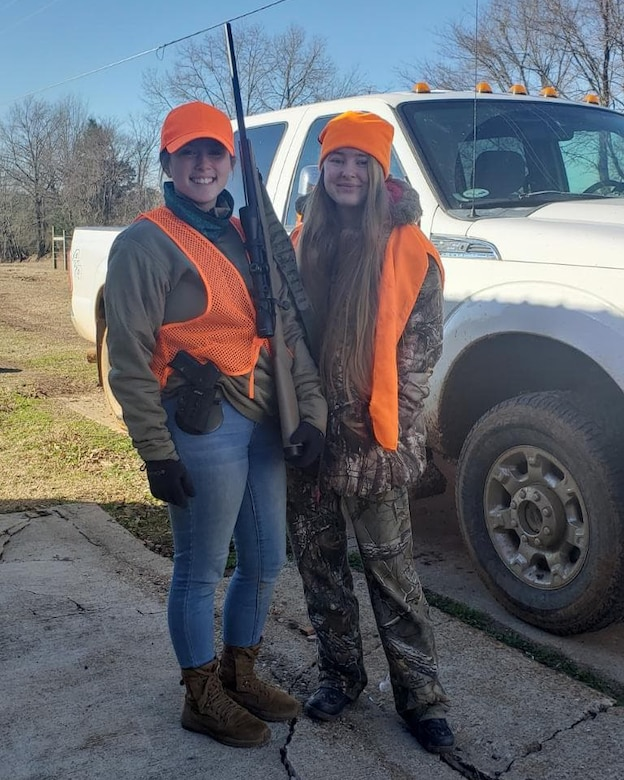 Two women in hunting clothes pose for a photo with a rifle.