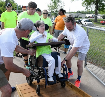 AEDC team members Brian Allen, left, and Mark Jenkins, right, assist Sean Couch, a Tullahoma Skills Development Services employee, in maneuvering athlete Christie Tippy Pittman and her wheelchair into the track at Tullahoma High School May 2, 2019, for the Tennessee Area 13 Special Olympics 2019 Spring Games. (U.S. Air Force photo by Jill Pickett)