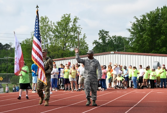 AEDC team member Master Sgt. Matt Krueger carries the U.S. flag as fellow team member Technical Sgt. Richard Griffin waves, both stationed at Arnold Air Force Base, to lead the parade of the opening ceremonies of the Tennessee Area 13 Special Olympics Spring Games May 2, 2019 at Tullahoma High School. (U.S. Air Force photo by Jill Pickett)