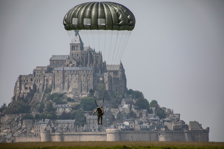 A soldier attached to a parachute descends in front of a giant fortress.