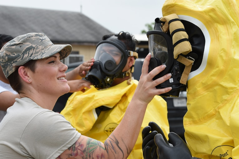 An airman places a hand over the mask of another airman in a hazmat suit.