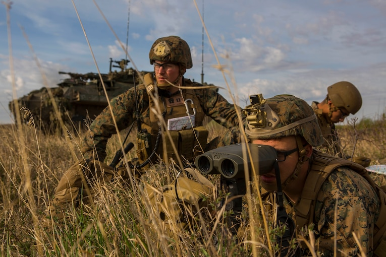 A service member looks through binoculars while lying in tall grass in front of an armored vehicle as others look on and check a map.