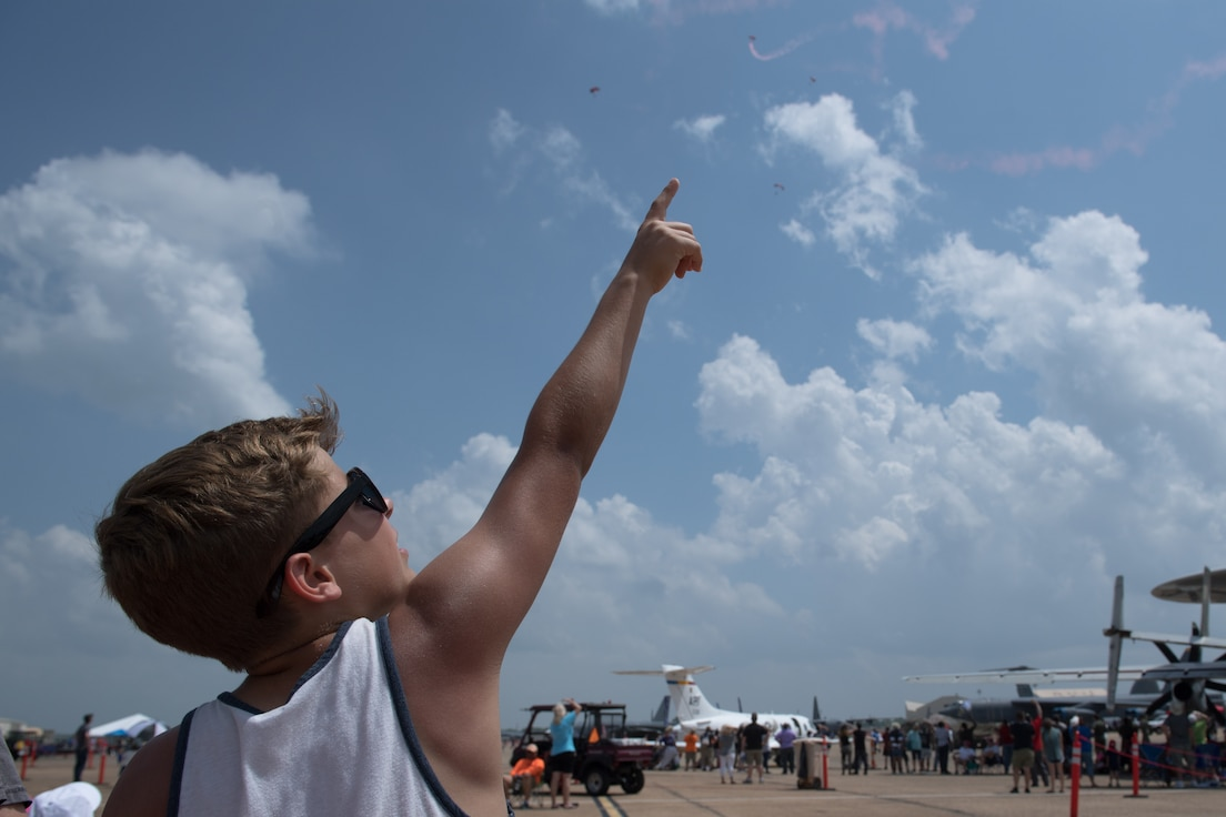 A spectator watches the U.S. Army Special Operations Command Black Daggers Parachute Demonstration Team perform during the Defenders of Liberty Air & Space Show at Barksdale Air Force Base, La., May 19, 2019.  The airshow was first held in 1933 and is a full weekend of military and civilian aircraft and performances and displays. (U.S. Air Force photo by Senior Airman Stuart Bright)