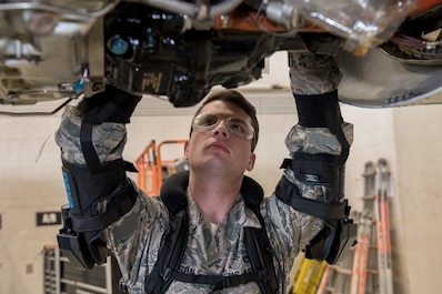 U.S. Air Force Staff Sgt. Christian Watson, an aircraft electrical environmental technician with the 461st Air Control Wing, demonstrates the use of an exoskeleton vest for maintenance on an E-8C Joint STARS at Robins Air Force Base, Ga., Feb. 26, 2019. The exoskeleton vest is part of an innovative practice to relieve muscle stress during long jobs where maintainers are working overhead. (U.S. Air National Guard photo by Tech. Sgt. Nancy Goldberger)
