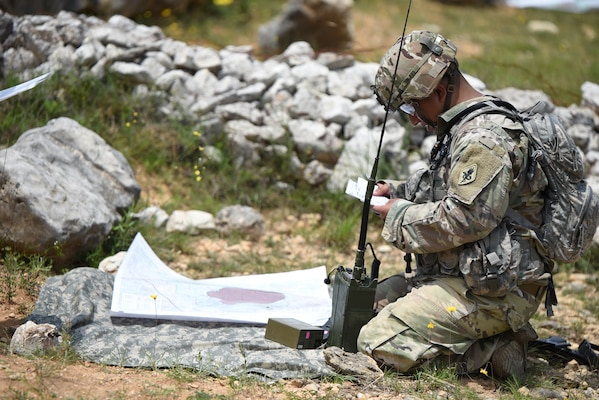 A Soldier assigned to the Training Support Activity, Army Medical Department Center & School, Health Readiness Center of Excellence, training at Joint Base San Antonio-Camp Bullis, reviews a 9 Line MEDEVAC request before calling it in over a radio.