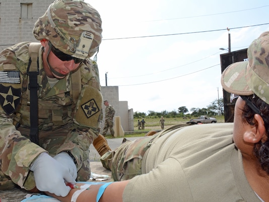 A 68W Combat Medic assigned to the 32nd Medical Brigade practices delivering intravenous fluid at a tactical combat causality care training event at Joint Base San Antonio-Camp Bullis.
