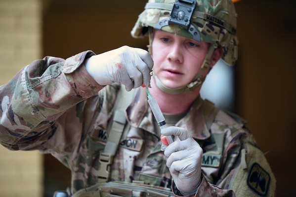 A 68W Combat Medic attending the Army Medical Department Center & School, Health Readiness Center of Excellence Noncommissioned Officers Academy Advanced Leader Course prepares an injection.