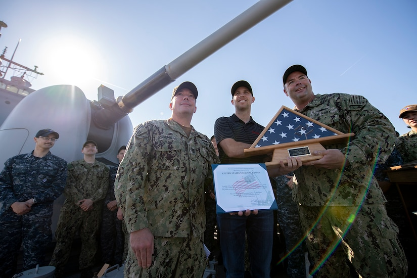 A civilian stands with sailors on the deck of a ship while holding a framed U.S. flag and a certificate. An MK 45 5-inch lightweight gun is in the background.