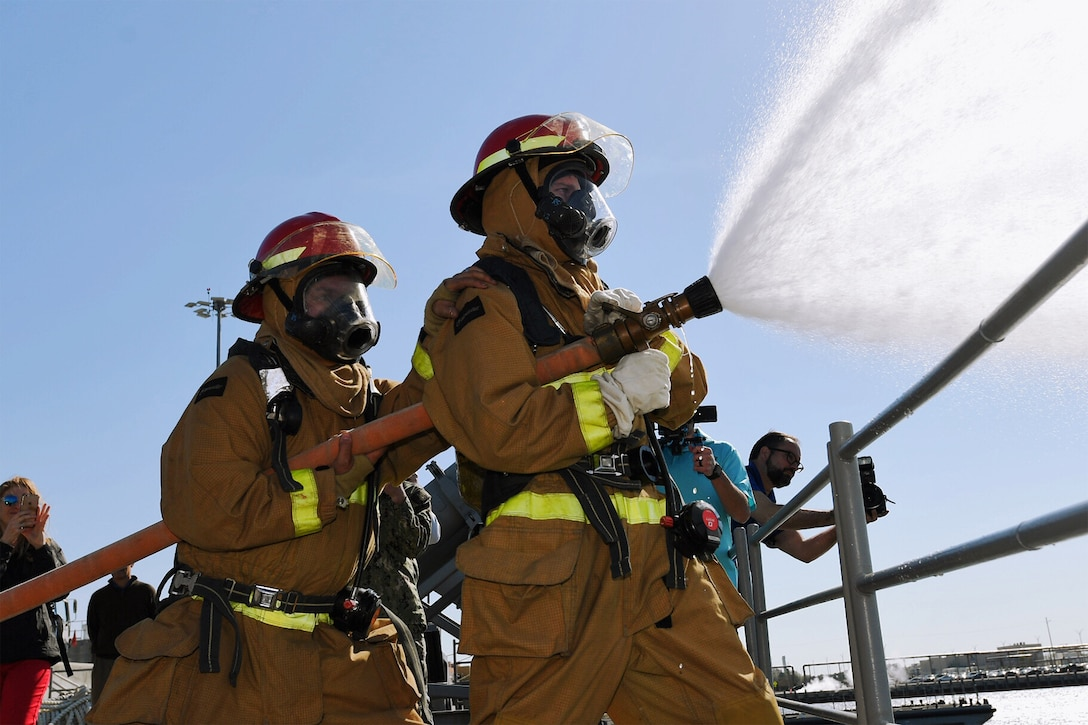 Two men in firefighter gear spray a fire hose off the deck of a ship as two men in the background take photos.