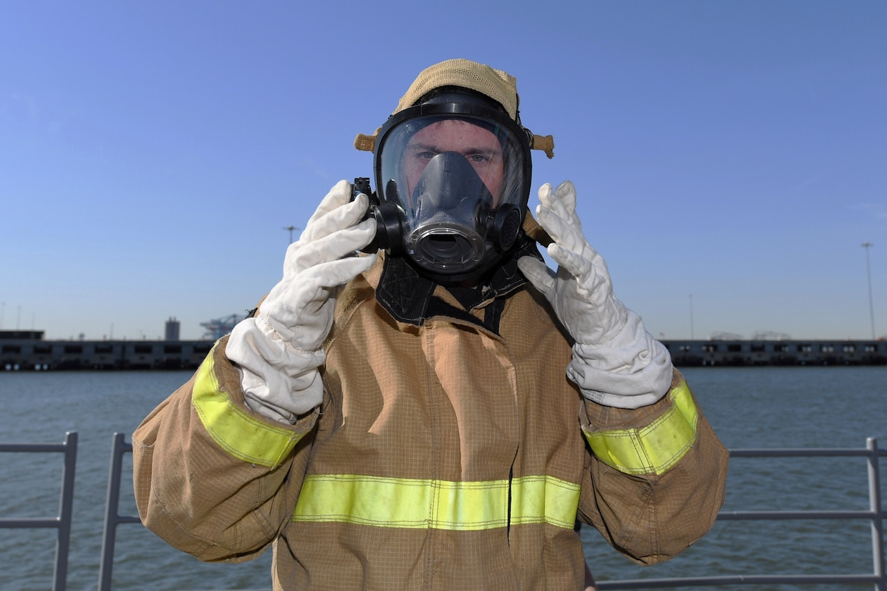 A man on the deck of a ship wearing a firefighting suit adjusts the mask he's wearing with gloved hands.