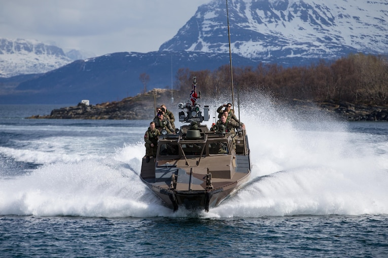 Marines speed across water on a boat with snow capped mountains in background.