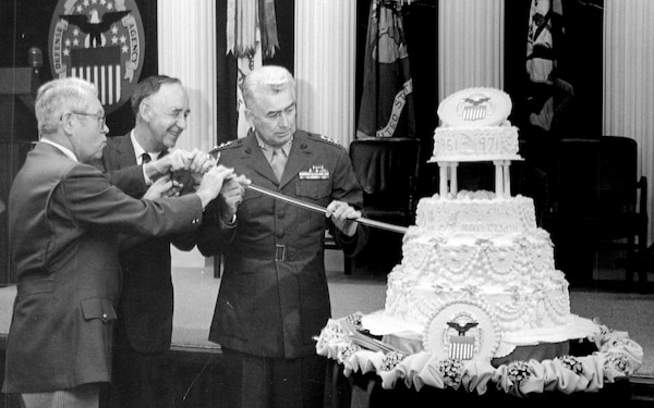 Former Defense Supply Agency directors Army Lt. Gen. Andrew T. McNamara, Navy Vice Adm. Joseph M. Lyle and Marine Lt. Gen Wallace H. Robinson, Jr. cut a cake