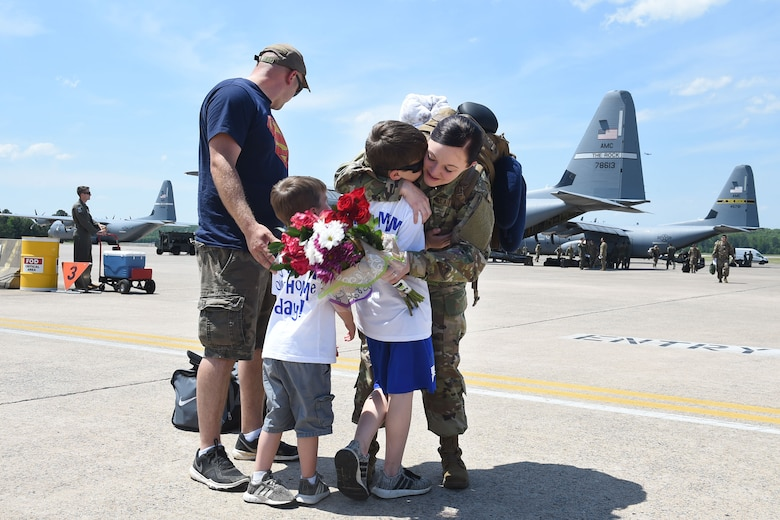 A female Airman hugs her two sons on the flight line