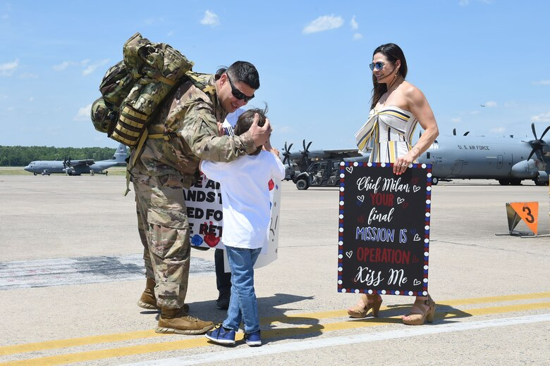 An Airman hugs his son while his wife looks upon them on the flight line