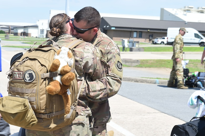 A female Airman hugs her husband on the flight line