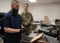 """Michael Liang and Air Force Staff Sgt. Matthew Furlough, Precision Measurement Equipment Laboratory technicians, place two blocks together to create """"wringing,"""" on Joint Base McGuire-Dix-Lakehurst, New Jersey, April 10, 2019. """"Wringing"""" takes two flat surfaces and vacuum seals the blocks together with no air molecules in between. (U.S. Air Force photo by Senior Airman Jake Carter)"""