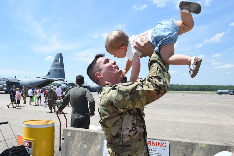 An Airman holds his small child in the air