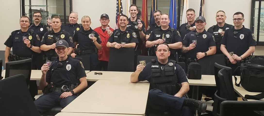 Swing Shift at Police Department posing with coin, some sitting, some standing