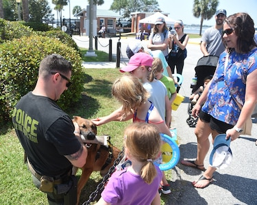 """The Charleston Police Department holds a """"meet-and-greet"""" for families to interact with law enforcement working dogs and their handlers, who are often employed in both drug and explosive detection operations, during National Safe Boating Week May 18, 2019, at U.S. Coast Guard Sector Charleston in Charleston, S.C. The U.S. Coast Guard often coordinates with local authorities to augment their mission of maritime law enforcement. The Coast Guard National Safe Boating Week Campaign is an annual week-long event held every May to promote boating safety and to inform the public on proper boating procedures. Federal law mandates that the U.S. Coast Guard establish the National Boating Safety Advisory Council and consult with it on regulations and other major boating safety matters. (U.S. Air Force photo by Senior Airman Cody R. Miller)"""