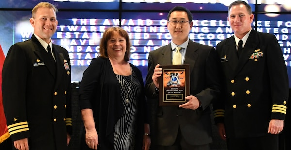IMAGE: Michael Huang receives the Award of Excellence for  Systems Engineering and Integration at the annual honorary awards ceremony, May 10.  Standing left to right: NSWCDD Dam Neck Activity Commanding Officer Cmdr. Andrew Hoffman; NSWCDD Deputy Technical Director Angela Beach; Huang; and NSWCDD Commanding Officer Cmdr. Stephen 'Casey' Plew.